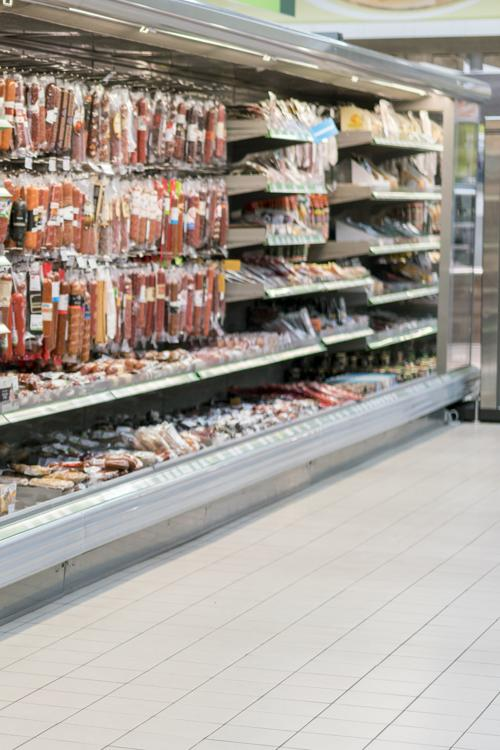 Shelves with sausage and meat products in the supermarket. blurry