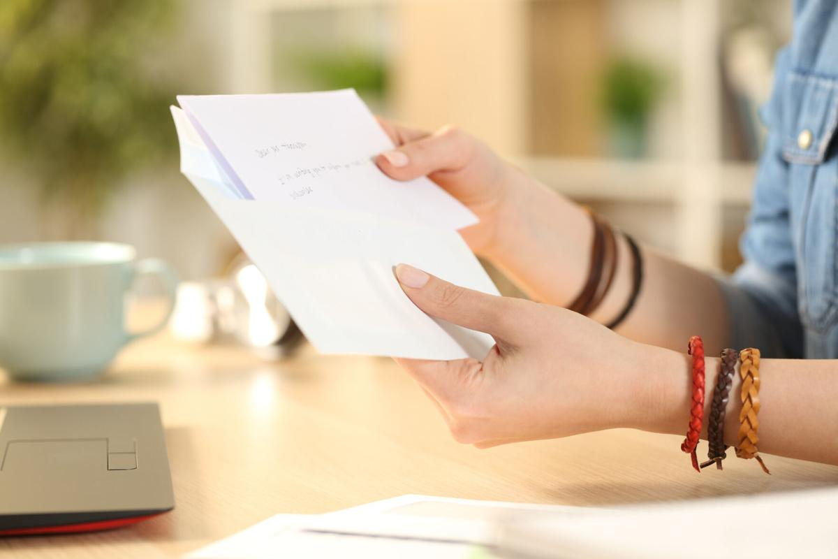 Student girl hand putting letter on an envelope at home