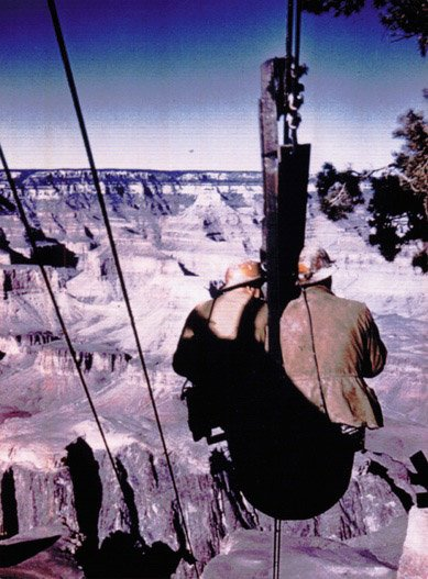Workers riding an ore bucket over the Grand Canyon