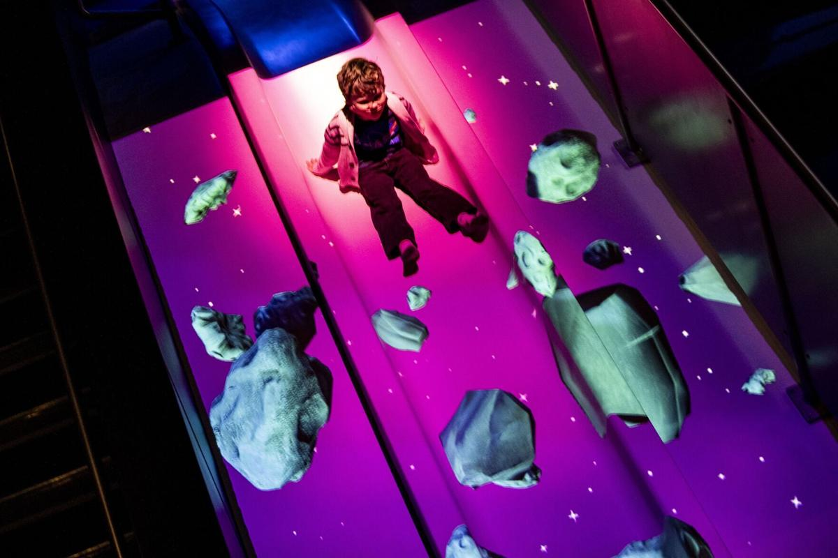 Eli Willis, 4, of Titusville, slides down a slide with projected asteroids in Planet Play at Kennedy Space Center Visitor Complex on Monday, Jan. 4, 2021.