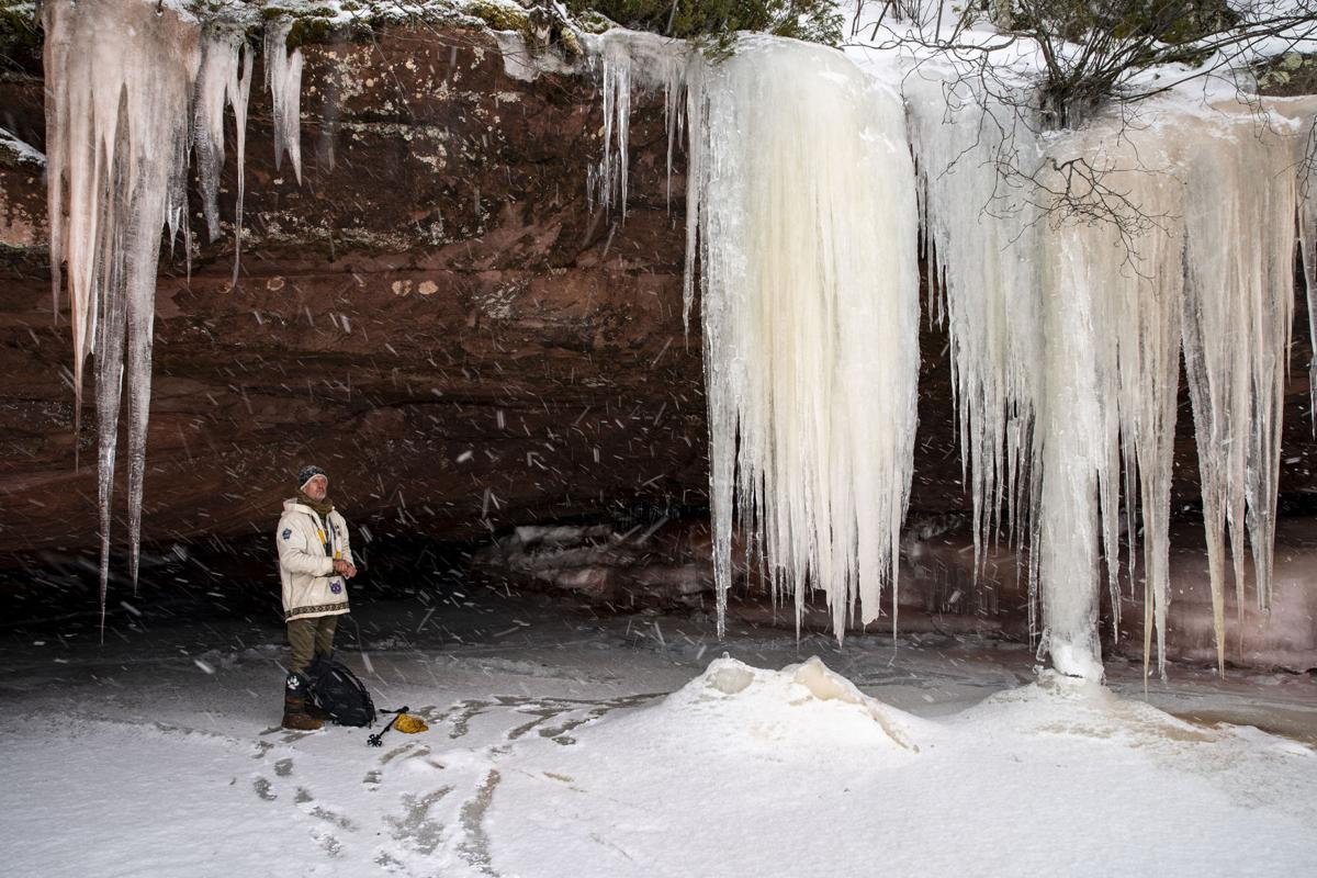 "Jon Michaels, one of the two guides for the Red Cliff Point guided ice cave tour, takes in the view of falling snow from inside a cave nicknamed ""root beer float"" on Wednesday, Feb. 26, 2020."