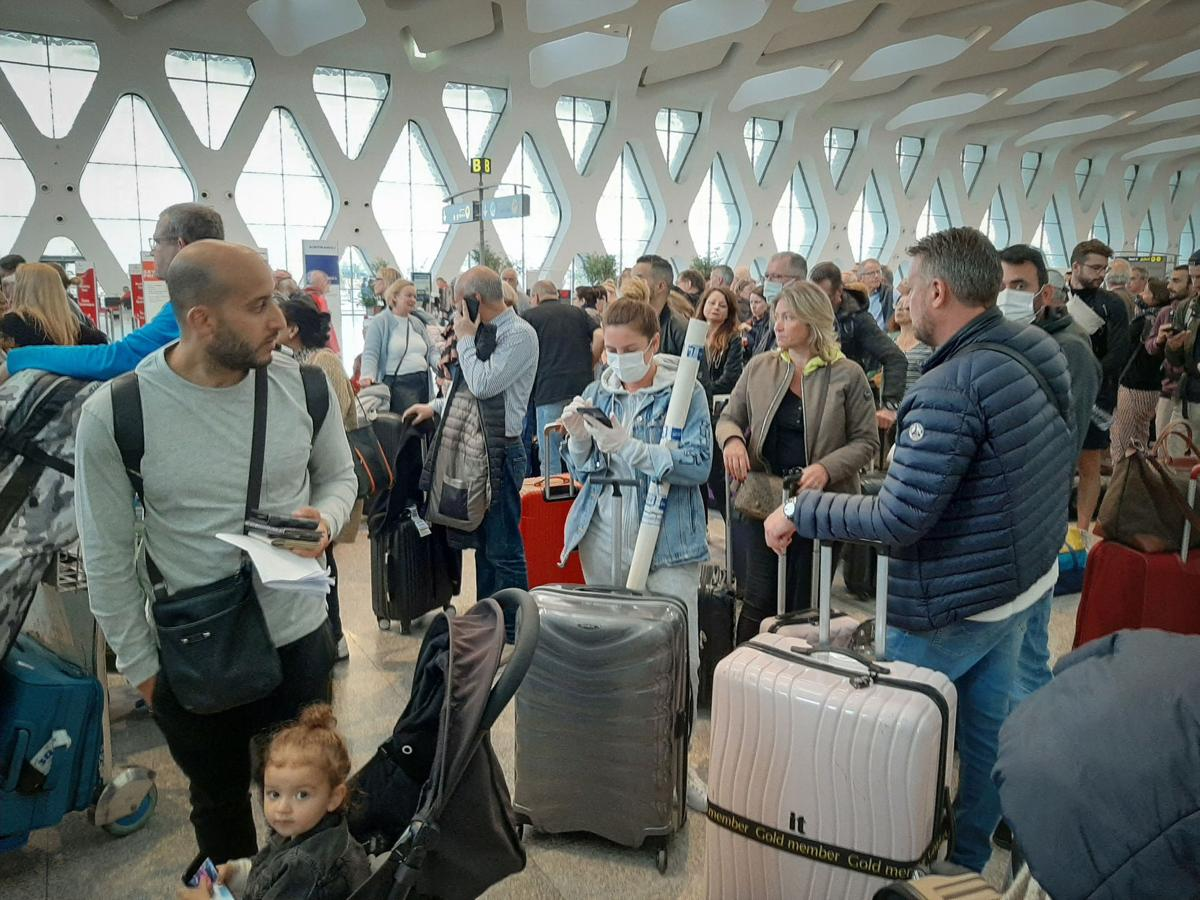 Passengers wait for their flights at the Marrakesh Airport on March 15, 2020. Several special flights departed Morocco, taking thousands of stranded Europeans home as the kingdom announced it was suspending all regular air traffic due to the coronavirus, authorities and airports said.