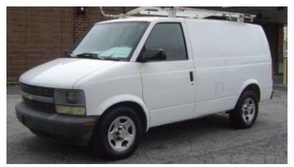 Older-model, white van with a ladder on the roof
