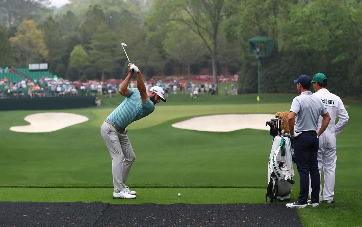 Rory Mcllroy looks on as Dustin Johnson tees off on the par-3 hole number 4 during their practice round for the Masters at Augusta National Golf Club on Monday, April 8, 2019 in Augusta, Ga.