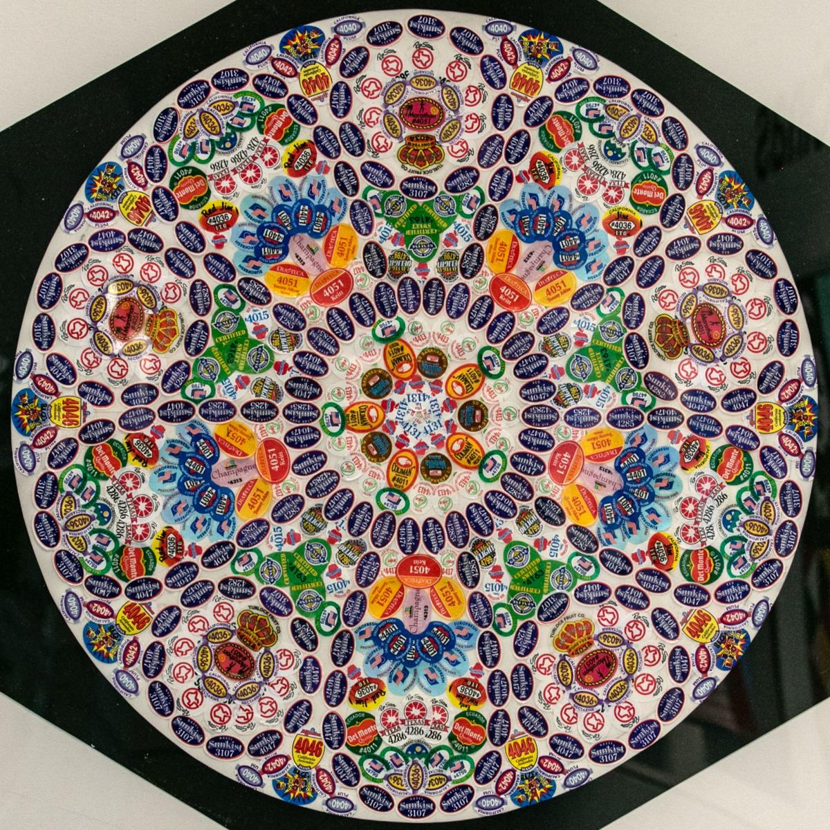 A circular, mandala-like collage made from fruit stickers that resembles a church window.