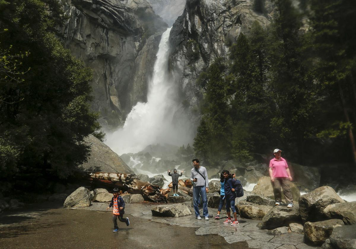 Visitors stand in a mist cloud while they snap pictures of the gushing Lower Yosemite Fall in the Yosemite Valley May 5, 2017.