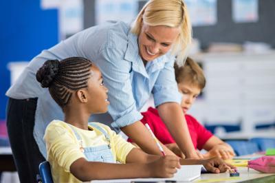 Happy teacher helping her students at elementary school. Teacher help schoolgirl and schoolboy writi