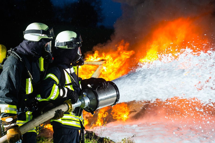 Firefighter - Firemen extinguishing a large blaze, they are standing with protective wear in front o
