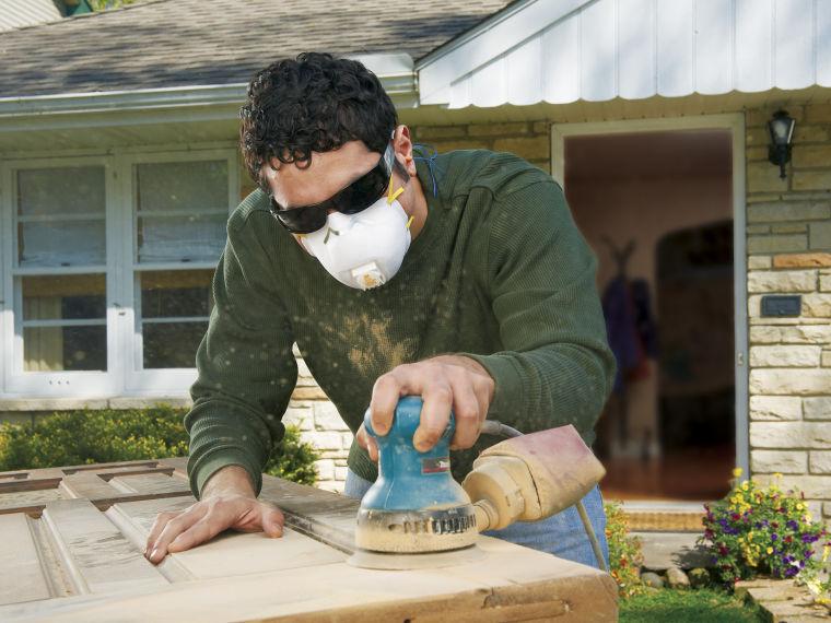 Man sanding door