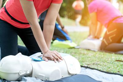 Asian Female Or Runner Woman Training Cpr Demonstrating Class In Park By Put Hands And Interlock Fin