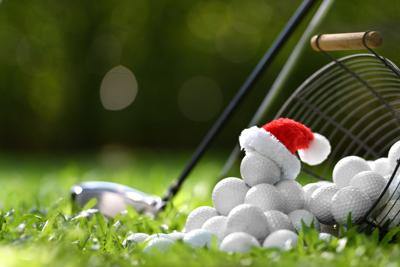 Festive-looking Golf Ball On Tee With Santa Claus' Hat On Top For Holiday Season On Golf Course Back