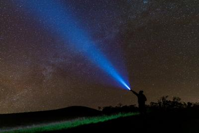 Climber Or Backpacker. Light Holds Up Over His Head. Standing On Mountain Peak. Man With Flashlight