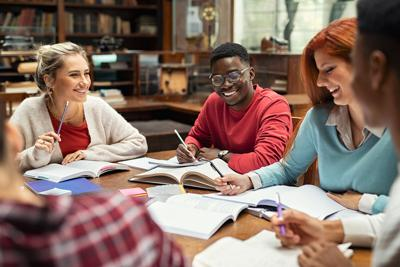 Happy college students studying together and laughing. Group of multiethnic friends smiling and stud