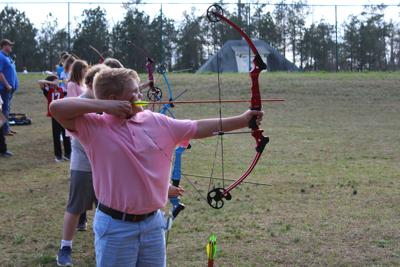 8b83cba59973 A young archer takes aim at his target. JMA received bows, arrows and  targets to start its archery program through a grant from NASP.