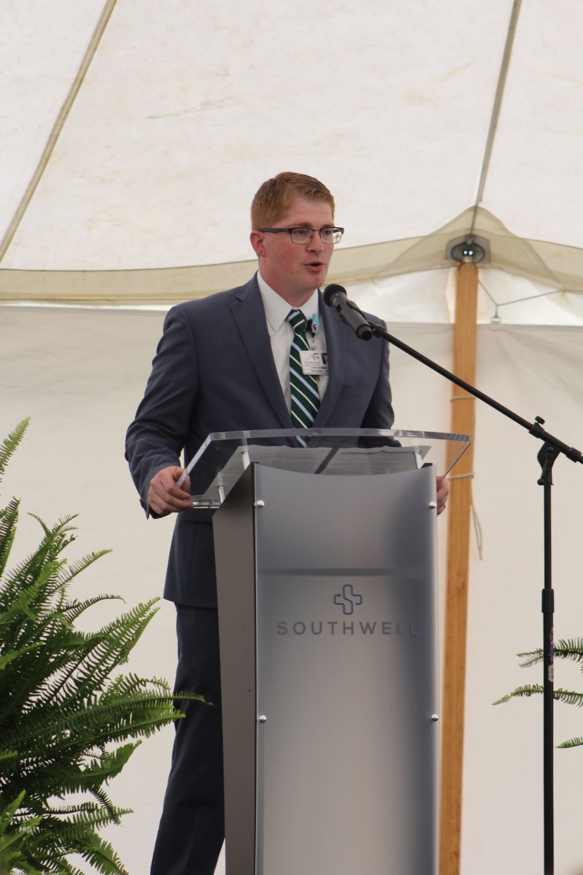 Southwell President and CEO Christopher Dorman addresses the crowd before the ceremonial groundbreaking for the new patient tower. The podium bears the new Southwell system name.