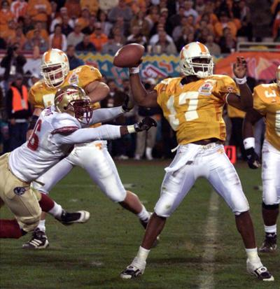 Tennessee Volunteers Quarterback Tee Martin 17 Gets Off A Long Pass Despite The Pressure Of Florida States Roland Seymore 56 During Fiesta