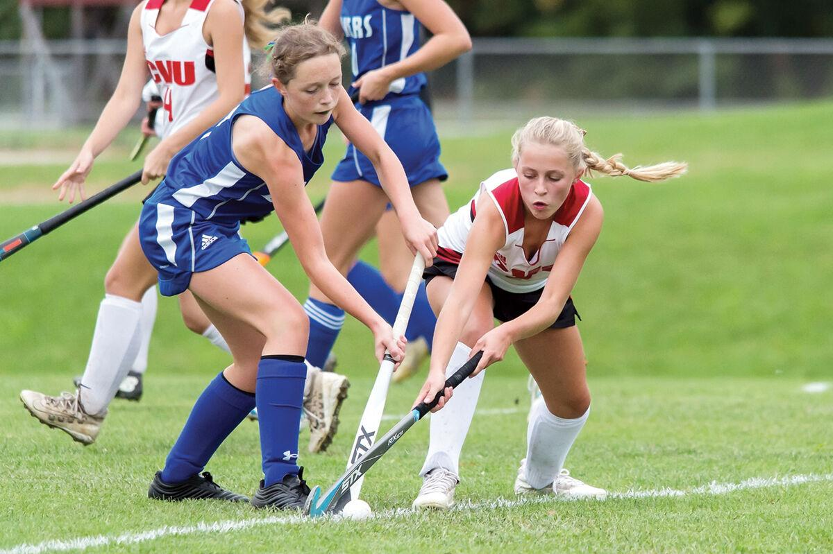 A Champlain Valley field hockey player battles for the ball