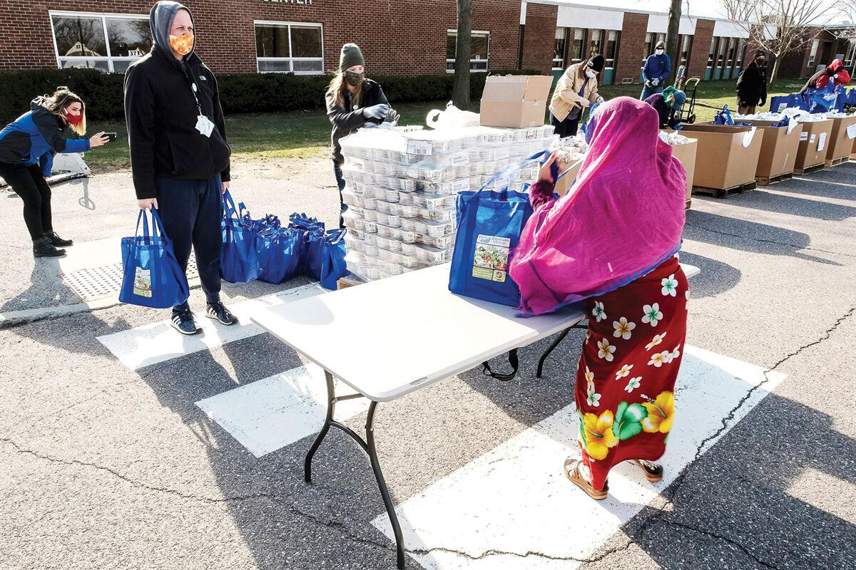 A woman grabs a meal bag from the Vermont Foodbank