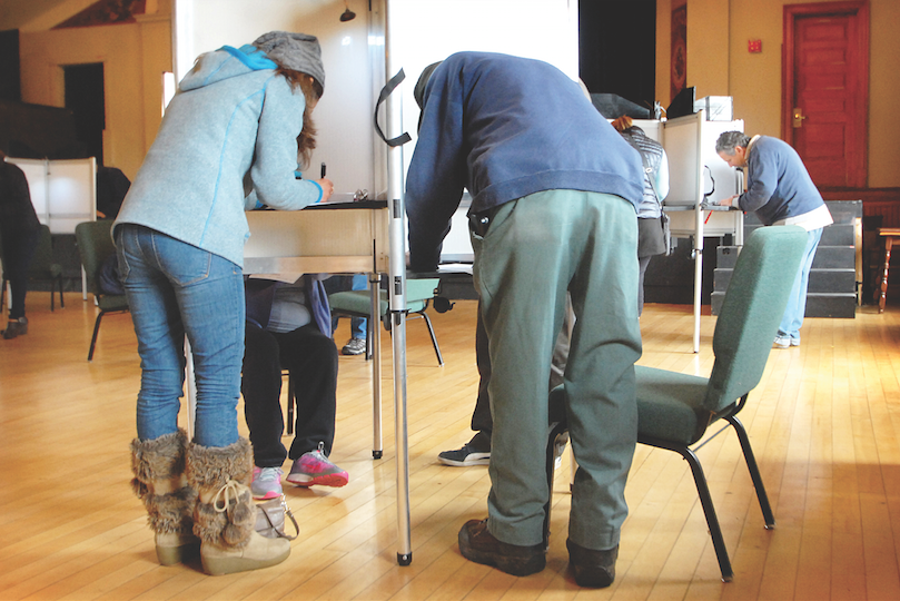 Voters fill in their ballots at the Akeley Memorial Building in Stowe on Tuesday.