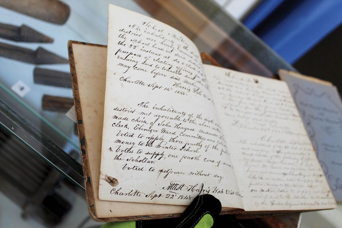 A book shows records from the 1800s in the Charlotte Historical Society museum