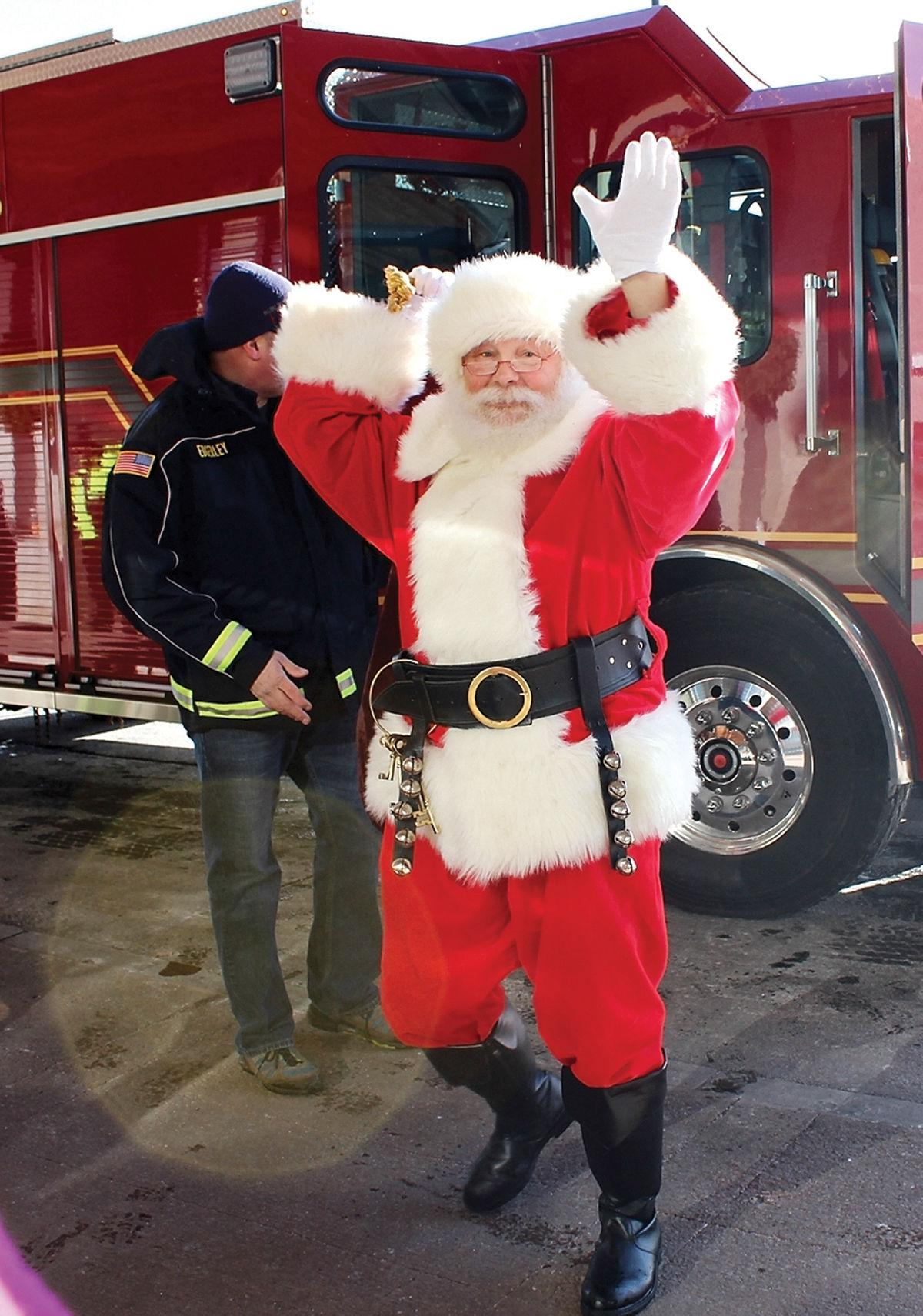 Santa dismounts a fire engine with a sack of toys for kids