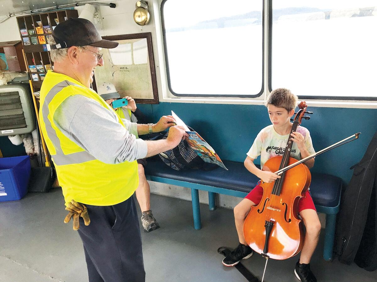 Oliver Hughes plays his cello on the ferry