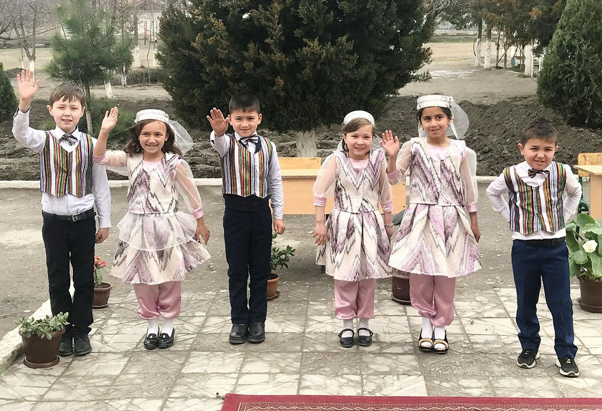 Second grade students greet visitors at their school in Uzbekistan