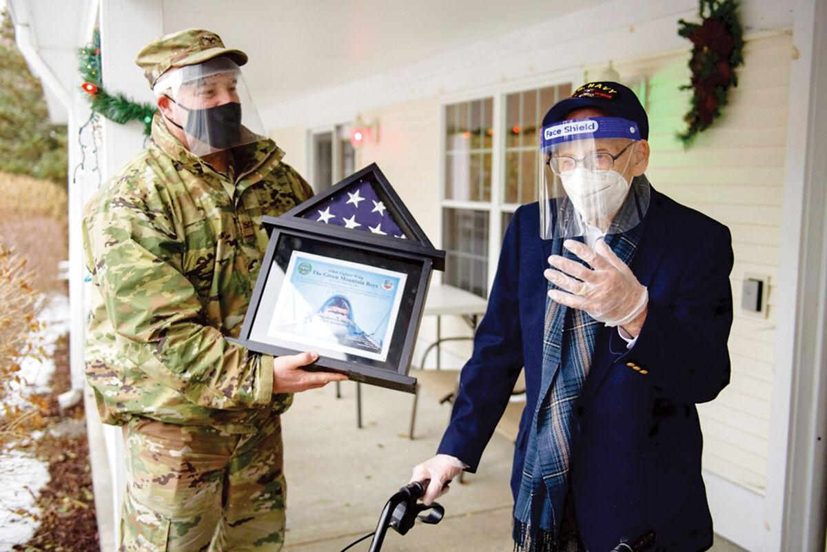 Col. Adam Rice presents a flag to Lenny Roberge