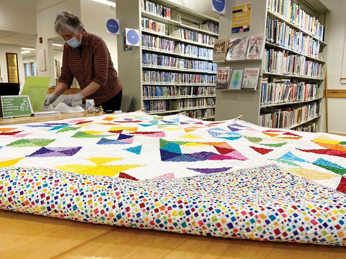 Library staff prepares to display a handmade quilt