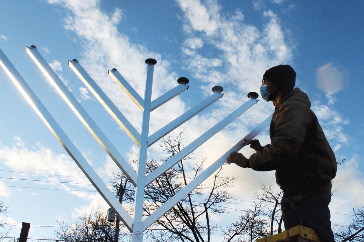 Andrew Keim prepares the menorah for lighting