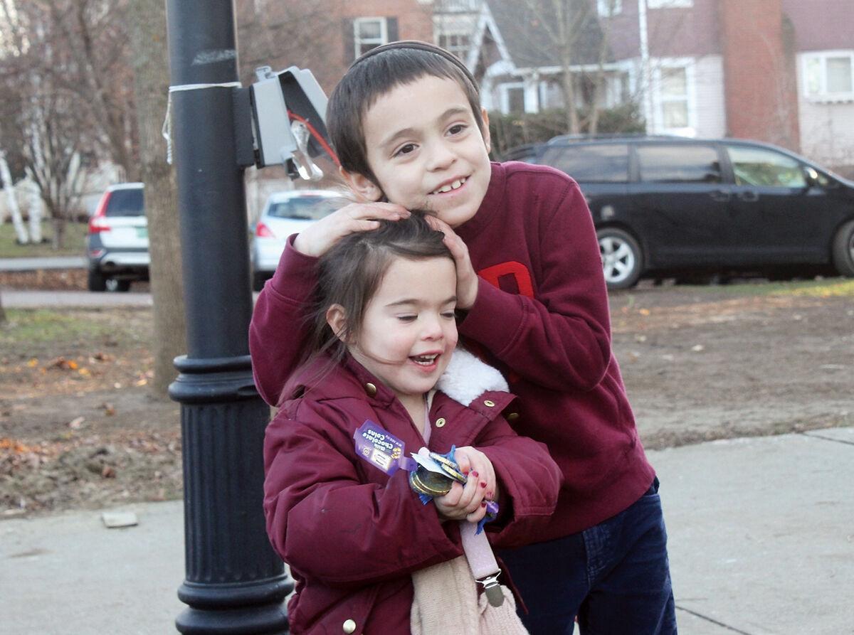 Musya and Ari Junik wait for Chabad of Burlington's menorah lighting celebration