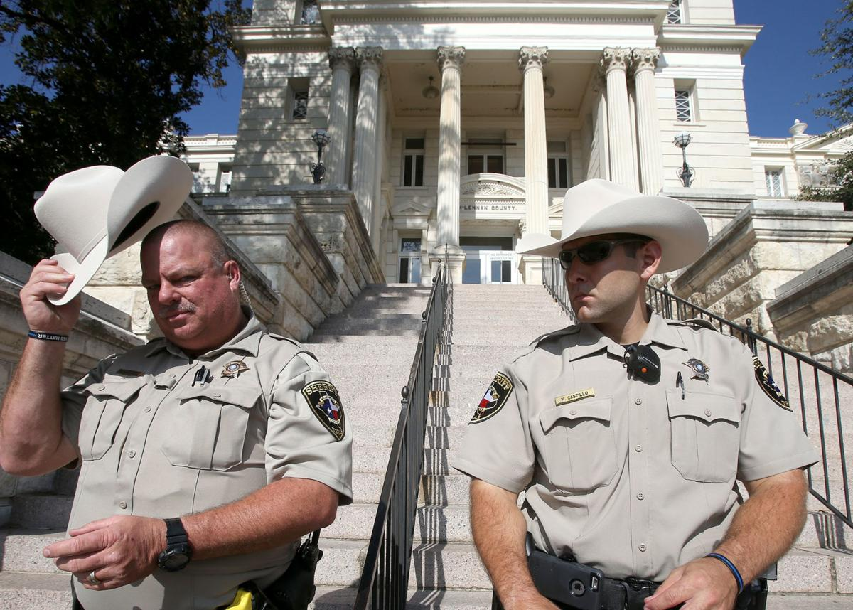 51e0f1cfc377c McLennan County Deputy Glenn Kennedy (left) places his hat on his head as  he and Michael Castillo stand outside the McLennan County Courthouse.