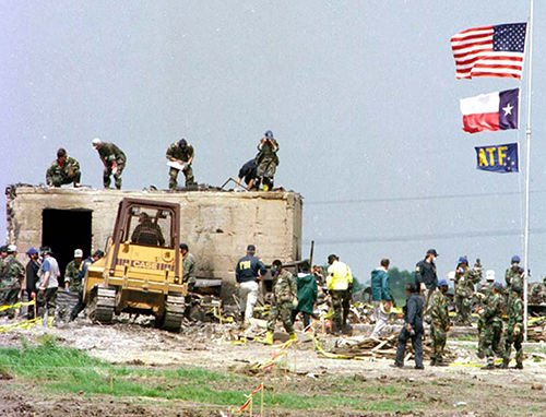 Law enforcement officers inspect the remains of the Branch Davidian compound following the fire.