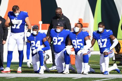In this file photo, New York Giants players kneel wearing face masks during the National Anthem before the first half against the Cincinnati Bengals at Paul Brown Stadium on November 29, 2020 in Cincinnati, Ohio.