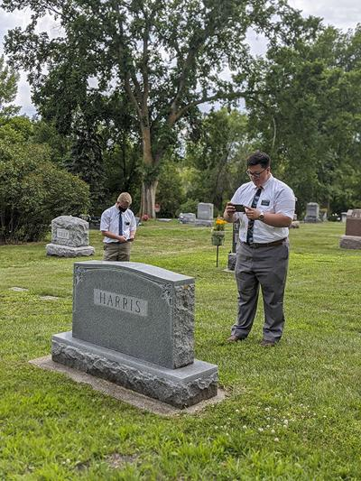 Missionaries in Wahpeton photographing cemetery headstones