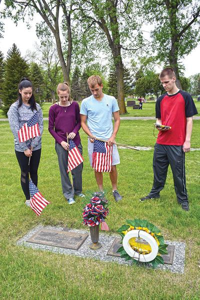 Students use technology to aid in placing flags at veterans' graves