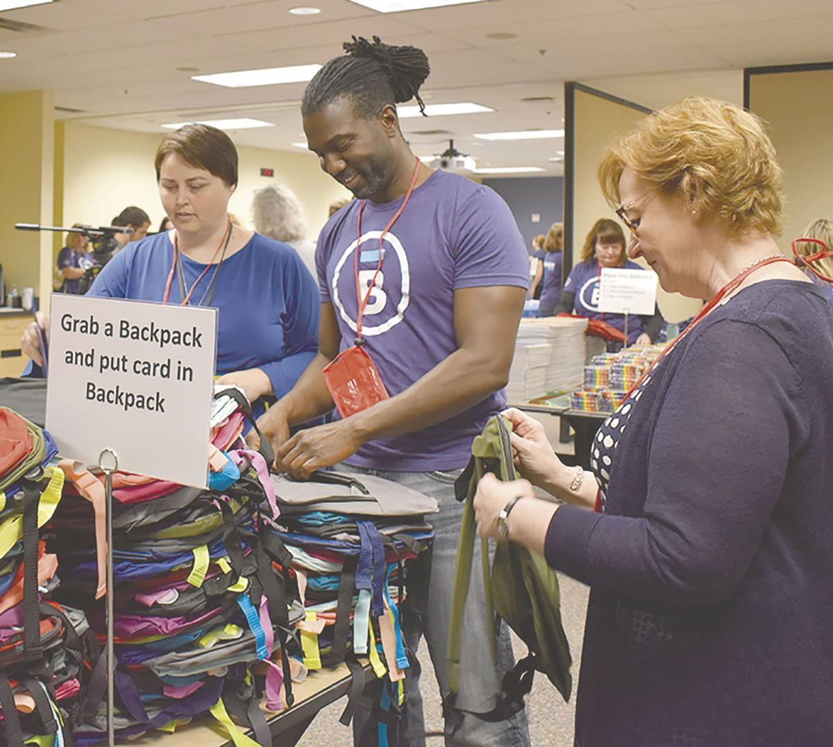 Bremer Bank volunteers stuff backpacks for students