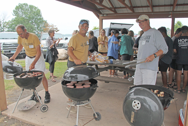 Al Sanford (from left), Steve Frick and Mark Vondenkamp prepare the burgers and brats for the barbecue.