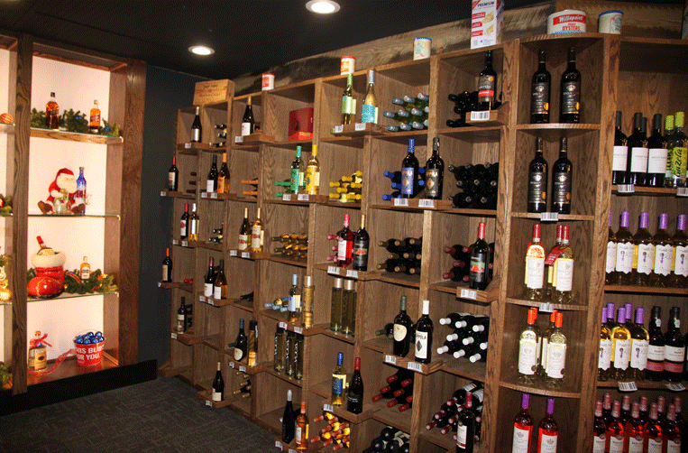 The liquor store has a large selection of wines lining a custom-built hardwood shelving.