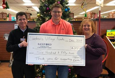 Pictured with the $652 check are (from left) Lueken's North Store Director Mike McNiel, Sanford Health Foundation Development Officer Cole Young and Lueken's South Store Director Shaylee Stately.