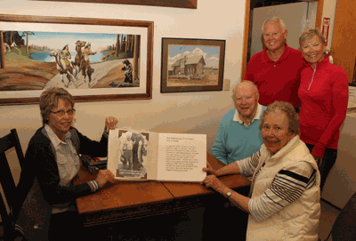 Janet Carlson (foreground right), shows Renee Geving the book she wote about Doc's Lodge as husband Roger Carlson, daughter Kristin Vlasak and son-in-law Gordon Vlasak look on. Carlson recently donated the book to the Cass County Historical Society.