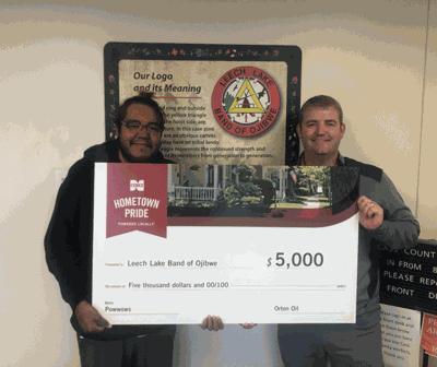 Branden Bowstring with the Ojibwe tribe (left) receives the $5,000 check from Frank Orton of Orton Oil.
