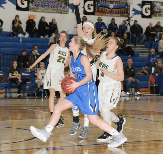 Kali Oelschlager drives past two Nevis defenders to score on this first-half play.