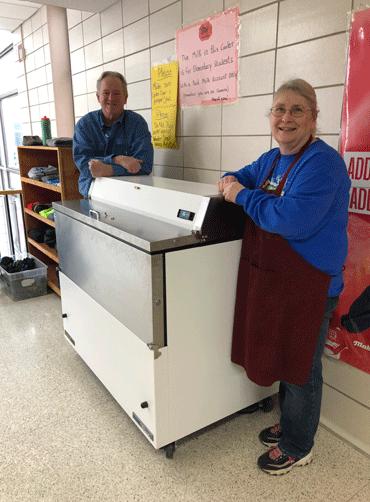 WHA head cook Nancy Semmler and Indian Ed Director Dr. Michael Anderson with the new milk cooler purchased using the grant money.