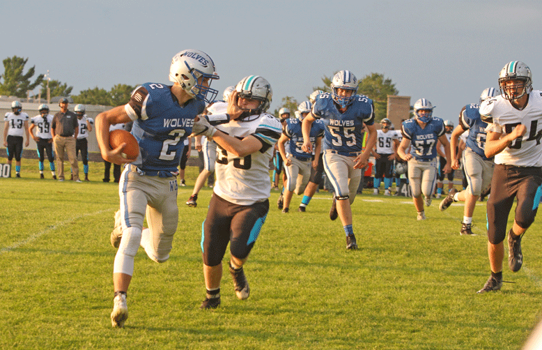 WHA quarterback Riley Welk uses a stiff-arm to fend off a defender on this first-quarter run.