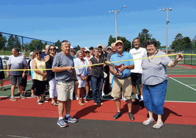 Many people came out for the official opening of the three new Pickle Ball courts in Walker City Park. Dave Cochran, who funded the project, cuts the ribbon as Steve Bilben and Walker Councilor Char Moore hold the tape during a ribbon-cutting ceremony July 22.