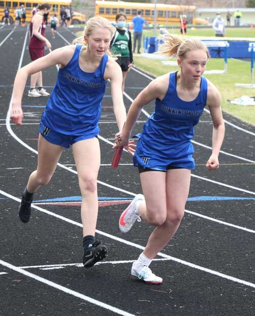 Erika Rand hands the baton to sister Britta Rand in the 800-relay where the Wolves took second.