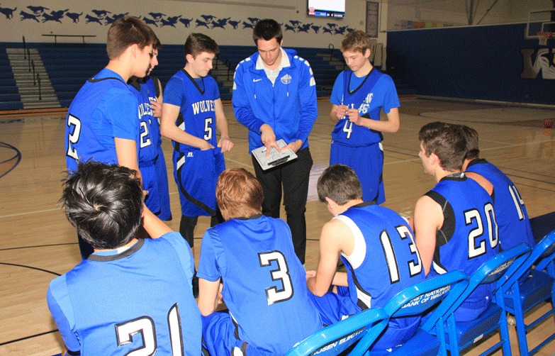 Coach Anthony Fisher breaks down a play for the players to run in their game against Mahnomen-Waubun.