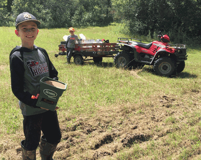 Jeff Weaver's grandsons Henrik and Anders Wolverton hand seeding a food plot.