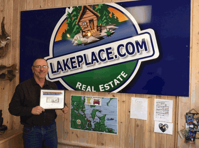 Pictured is Jim Flesch holding the First Business Dollar. Angie Schultz is also a realtor with LakePlace.com/Walker